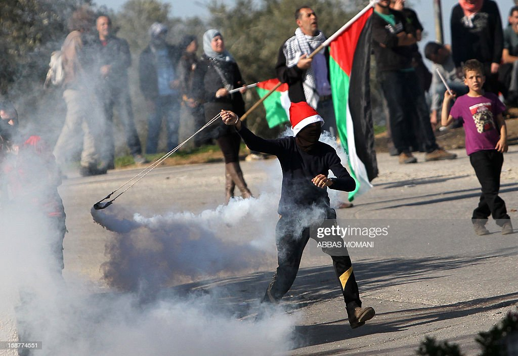 A masked Palestinian protester wearing a Santa Claus hat prepares to hurl back a tear gas canister fired by Israeli security forces during clashes that erupted following a march organised by residents of the West Bank village Nabi Saleh to protest against the expansion of Jewish settlements on Palestinian land on December 28, 2012.