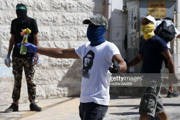 Masked Palestinian protesters throw molotov cocktails at Israeli security forces amidst clashes following Friday prayers in the Jerusalem Arab...