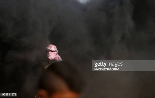 Masked Palestinian protestor stands amidst smoke from burning tires during clashes with Israeli forces on May 15, 2018 near the border fence with...