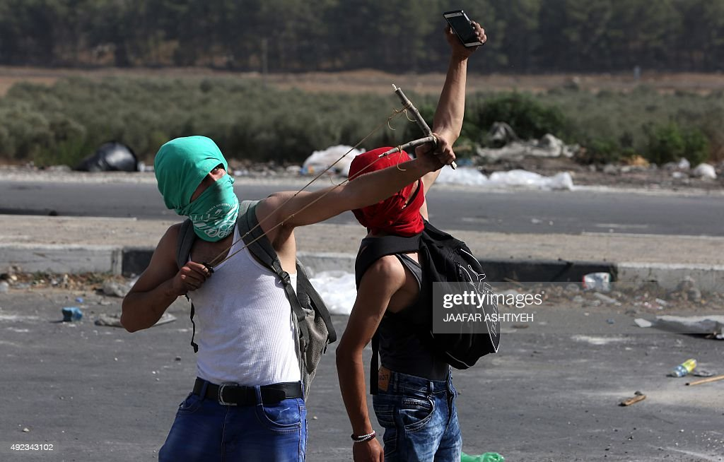 A masked Palestinian protestor takes a selfie as another one uses a sling shot to hurl stone towards Israeli security forces during clashes at the Hawara checkpoint, south of the West Bank city of Nablus, on October 12, 2015. Three new stabbings in Jerusalem and a car attack spread more fear among Israelis as Palestinian unrest showed little sign of slowing after nearly two weeks of violence.