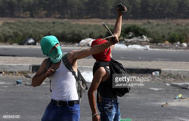 A masked Palestinian protestor takes a selfie as another one uses a sling shot to hurl stone towards Israeli security forces during clashes at the...