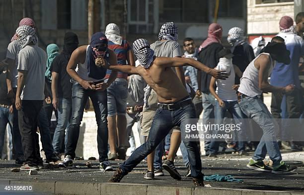 Masked Palestinian protestors throw stones toward Israeli police during clashes in Shuafat neighborhood in Israeli-annexed Arab East Jerusalem, on...