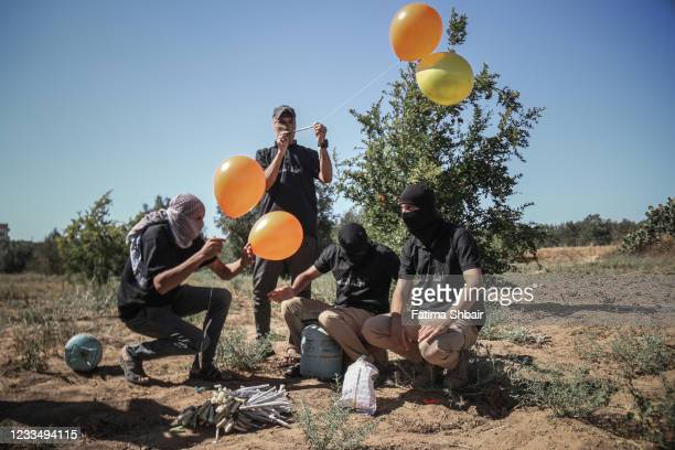 Masked Palestinian supporters of the Al-Nasir Salah Al-Din Brigades prepare incendiary balloons to launch across the border fence east of Gaza city...