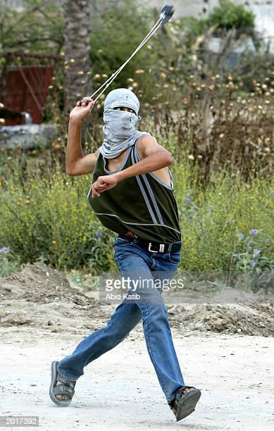 A masked Palestinian uses a slingshot to hurl stones at an Israeli tank May 21 2003 in Beit Hanoun Gaza Strip New Palestinian Prime Minister Mahmoud...
