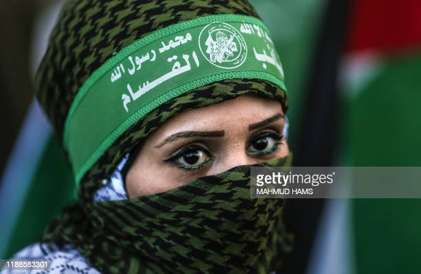TOPSHOT A masked Palestinian woman takes part in a march in Gaza city marking the 32nd anniversary of the founding of the Islamist movement Hamas on...