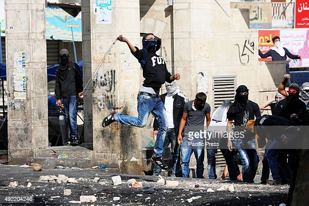 A masked Palestinian youth hurls a rock towards Israeli soldiers during clashes in the West Bank city of Hebron Intense clashes between Palestinian...