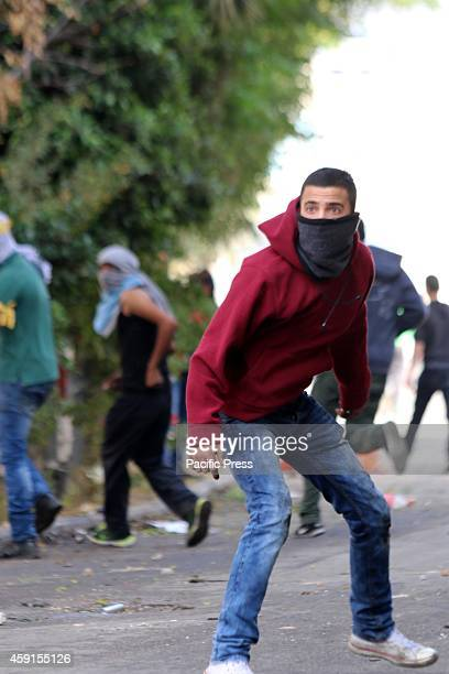 A masked Palestinian youth watches as Israeli soldiers advance in the streets of Abu Dis a Palestinian neighbourhood in Eastern Jerusalem Following...