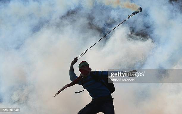 A masked Palestinian youth wearing a Hamas headband uses a slingshot to throw back a tear gas canister towards Israeli forces during clashes outside...