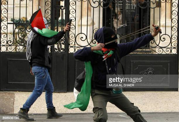 Masked Palestinian youths hurl stones towards Israeli forces during clashes following a protest against the US' decision to recognise Jerusalem as...