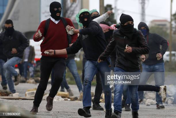 Masked Palestinian youths throw stones during clashes with Israeli soldiers on March 3 2019 following a protest by Birzeit University students near...