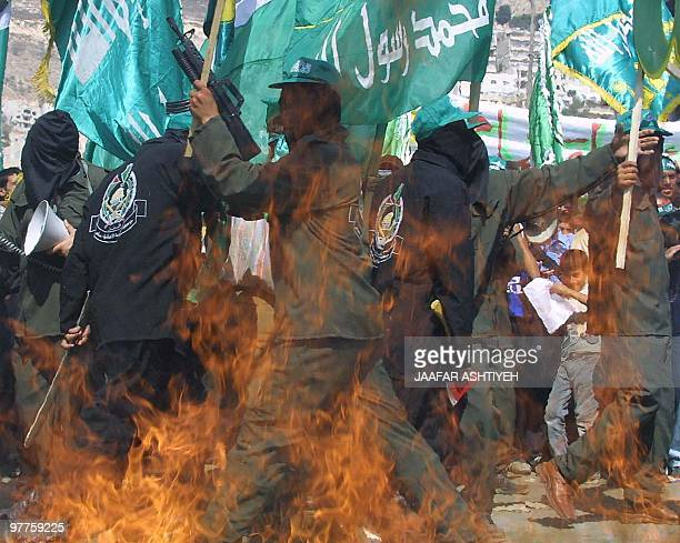 Masked Palestinians demonstrate to mark the third anniversary of the intifada in the northern West Bank town of Nablus 28 September 2003 A...