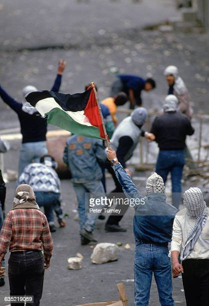 Masked Palestinians hold a flag and throw rocks at Israeli soldiers