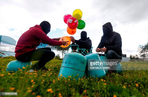 Masked Palestinians prepare to attach balloons to a gas canister before releasing it with an incendiary device near Gaza's Bureij refugee camp, along...