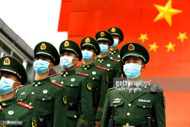 Masked paramilitary policemen rally before their duty shift in an area bordering Hong Kong in Shenzhen in south China's Guangdong province Monday,...