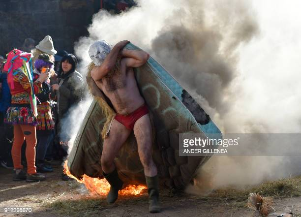 TOPSHOT A masked participant carries a burning matress during the ancient carnival of Zubieta in the northern Spanish Navarra province on January 30...