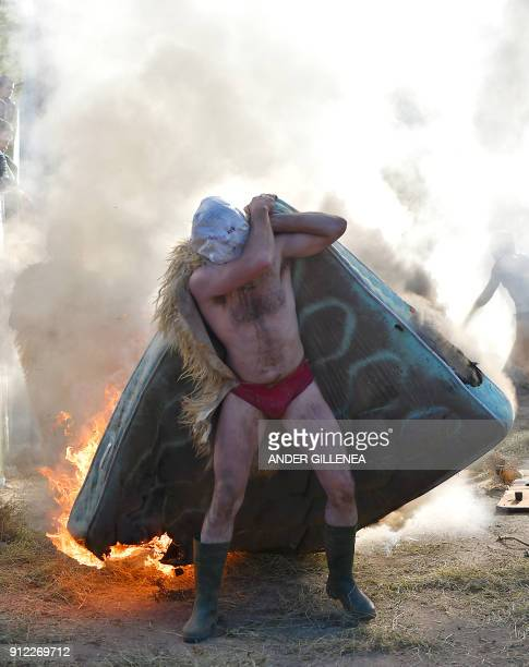 A masked participant carries a burning matress during the ancient carnival of Zubieta in the northern Spanish Navarra province on January 30 2018 The...