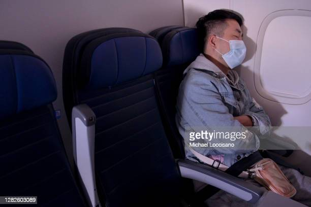 Masked passenger is seen sleeping on a flight from San Francisco, California to Newark, New Jersey on October 27, 2020. Although virus dissemination...