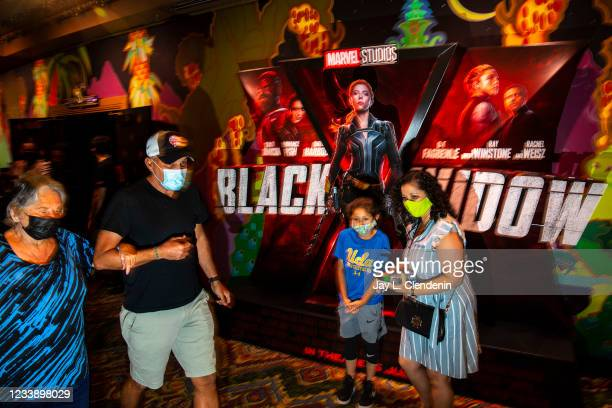 Masked patrons walk past a lobby display for Marvel Studios Black Widow, on opening weekend at the El Capitan Theatre, in the heart of Hollywood, CA,...