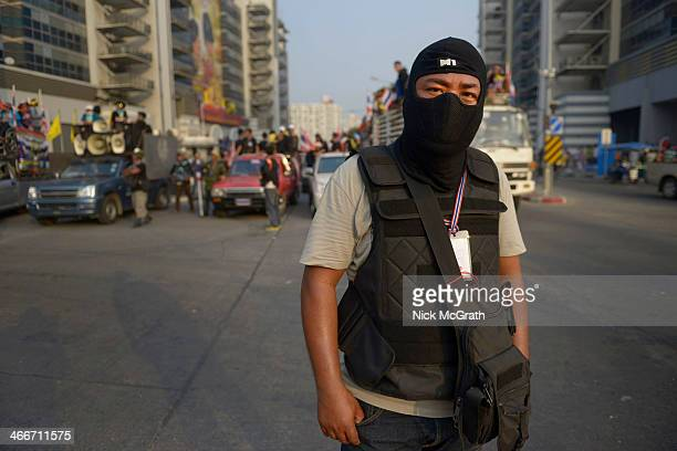A masked PDRC gaurd stands watch during anti government demonstrations on February 3 2014 in Bangkok Thailand The day after demonstrators disrupted...
