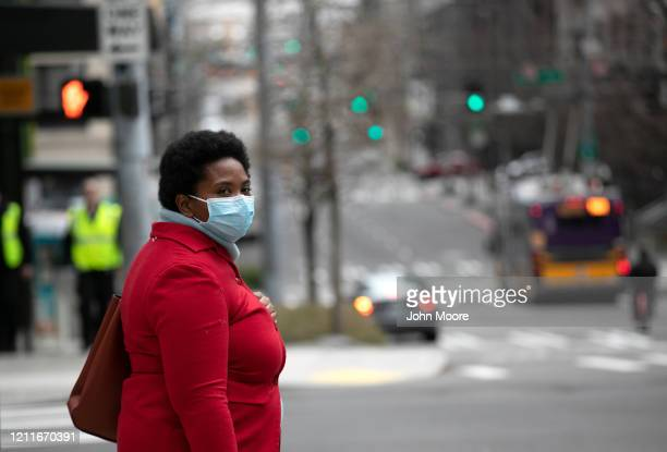 A masked pedestrian pauses near the Amazon headquarters on March 10 2020 in downtown Seattle Washington In response to the coronavirus outbreak...