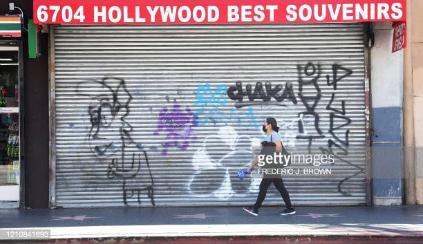 Masked pedestrian walks past shuttered shopfronts in Hollywood, California on April 23, 2020. - A record 26 million Americans have not been able to...