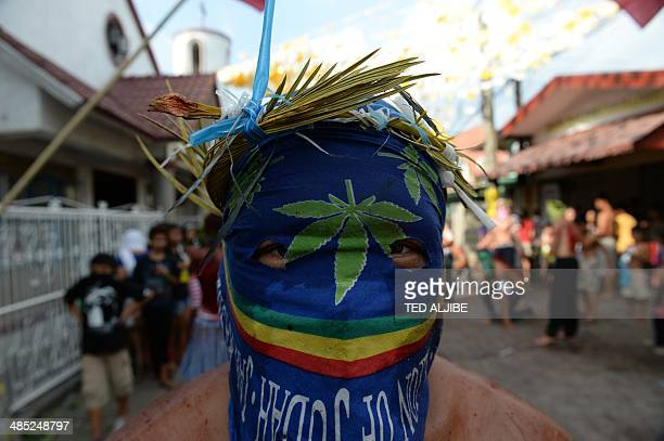 A masked penitent flagellates himself as part of Lenten observance in Angeles City Pampanga province north of Manila on April 17 2014 The dominant...