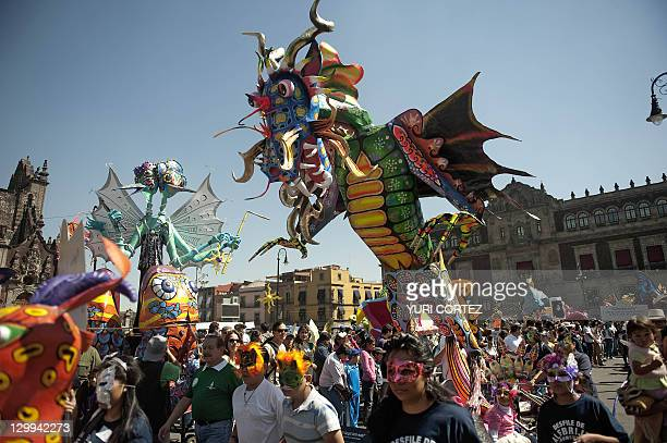 Masked people take part in the Fifth Monumental 'Alebrijes' Parade on October 22 2011 in Mexico City Some 250 'Alebrijes' brightly colored Mexican...
