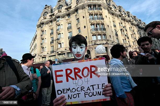 A masked person holds a placard reading 'Error 404 Democracy not found' as supporters of the antigay marriage movement 'La Manif Pour Tous'...