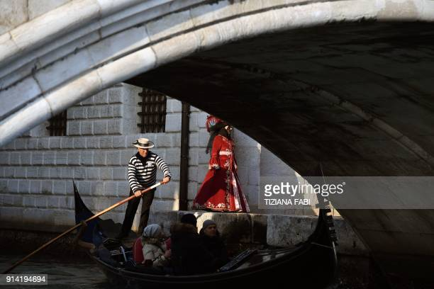 A masked person wearing a traditional carnival costume walks by a gondolier on his gondola in Venice during Venice's Carnival on February 4 2018 /...