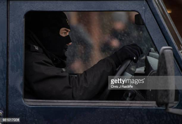 A masked police officer drives out of the upper level of a Sainsbury's supermarket car park opposite the park bench where Sergei Skripal was found...