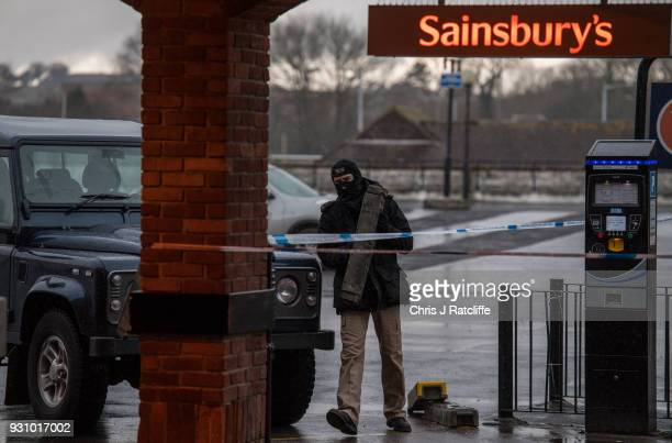 A masked police officer erects a barrier on the upper level of a Sainsbury's supermarket car park as it is cordoned off opposite the park bench where...