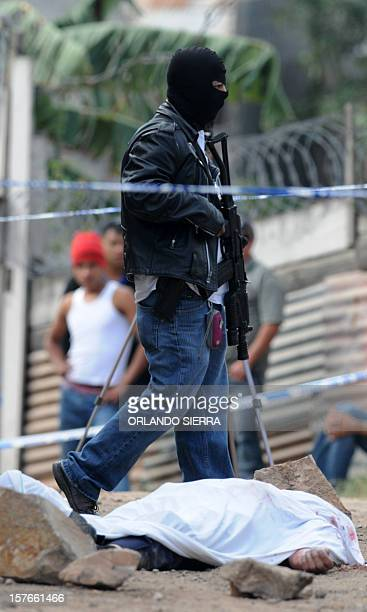 Masked policeman stands by the corpse of a fellow officer murdered presumably by gangsters to steal his handgun, in Tegucigalpa, on December 5, 2012....