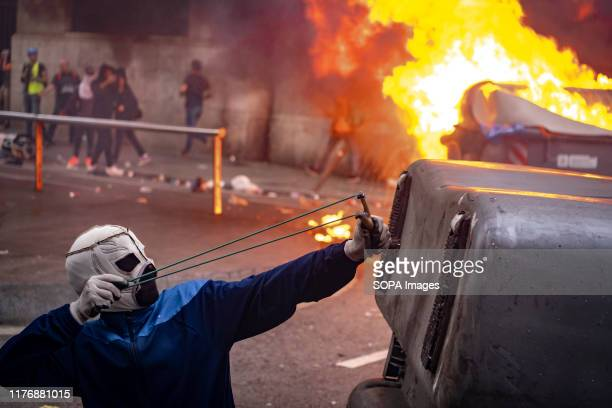 A masked protester aims a slingshot during the demonstration Fifth day of protest after the announcement of the sentences by the Supreme Court of...