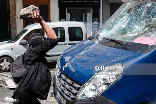 A masked protester dressed in black throws a stone to the windscreen of a vehicle prior to the start of May Day demonstrations in Paris on May 1 2019...
