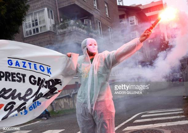 A masked protester holds a flare along with a banner reading in Basque 'Youth are ready We are with you' during a demonstration demanding the release...