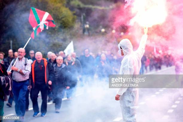 A masked protester holds a flare during a demonstration demanding the release of prisoners affiliated to the Basque separatist group ETA outside the...