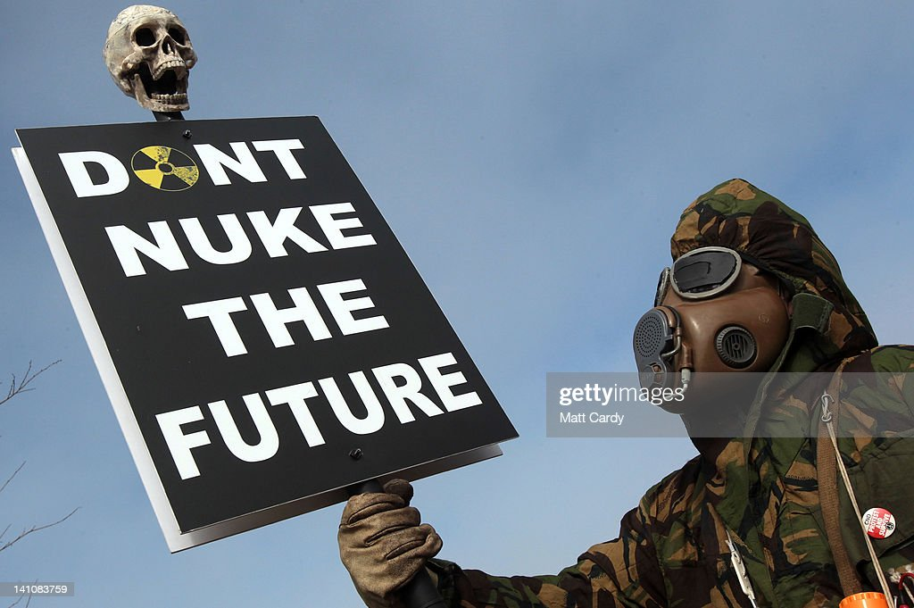 A masked protester holds a placard at the gates to the Hinkley Point nuclear power station to mark the first anniversary of the Fukushima disaster in Japan on March 10, 2012 near Bridgwater, England. Protestors planned to blockade the site at Hinkley, which is located on the Bristol Channel and has been earmarked for a potential new nuclear power station, for 24 hours starting today.