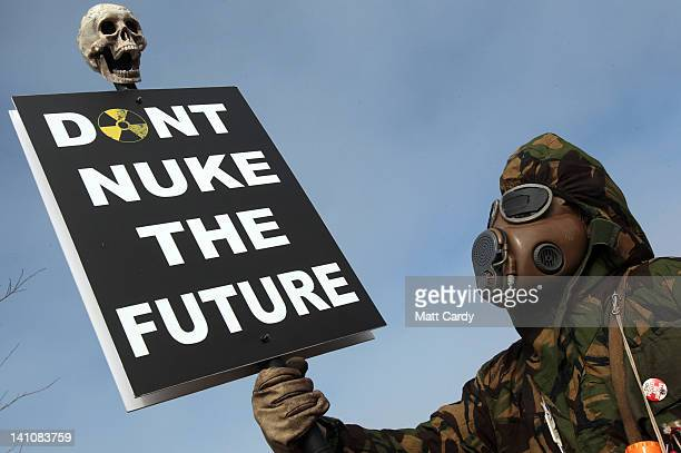 A masked protester holds a placard at the gates to the Hinkley Point nuclear power station to mark the first anniversary of the Fukushima disaster in...