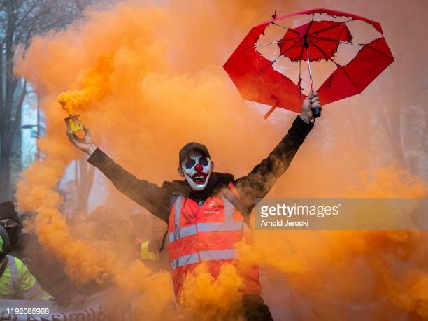 Masked protester holds a smoke grenade as public and private workers demonstrate and shout slogans during a mass strike against pension reforms on...