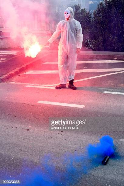 A masked protester lights flares during a demonstration demanding the release of prisoners affiliated to the Basque separatist group ETA outside the...