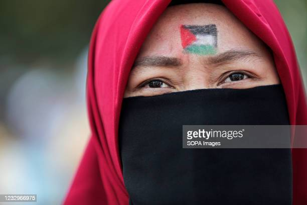 Masked protester looks on with a Palestinian flag painted on her forehead during the demonstration. Pro-Palestinian protesters marched to the heavily...
