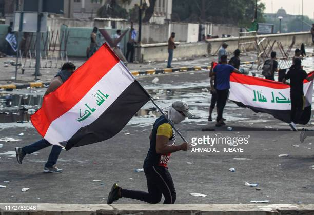 A masked protester runs with an Iraqi national flag amidst clashes with riot police during a demonstration against state corruption and poor services...