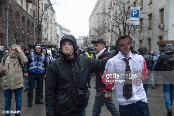A masked protester seen holding a mannequin with the face of oligarch Oleg Gladkovsky during the demonstration Thousands of people turned out to...