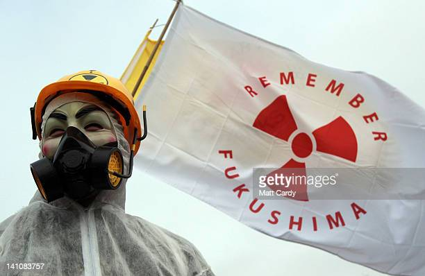 A masked protester stands in front of flags at the gates to the Hinkley Point nuclear power station to mark the first anniversary of the Fukushima...
