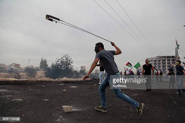 Masked protester throws rocks using slinger on Israeli army during clashes near Ramallah Clashes erupted between hundreds of Palestinian protesters...