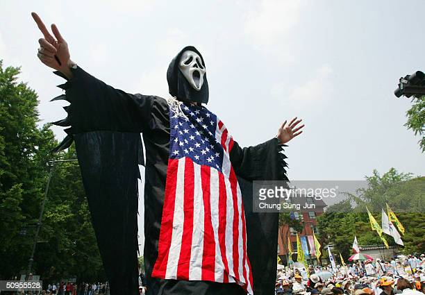 A masked protester wears a black gown during a rally against a meeting of the World Economic Forum near the Shilla Hotel where the Switzerlandbased...