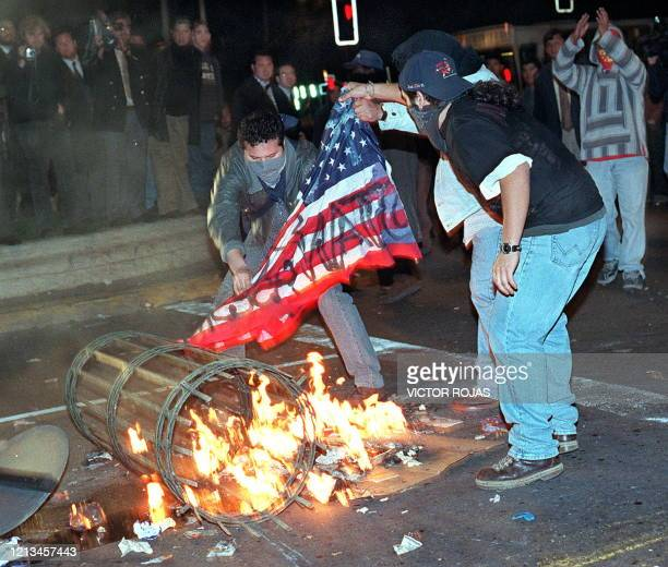 Masked protesters burn an American flag 10 August in Santiago as part of an organized protest against rising inflation and unemploymentEncapuchados...