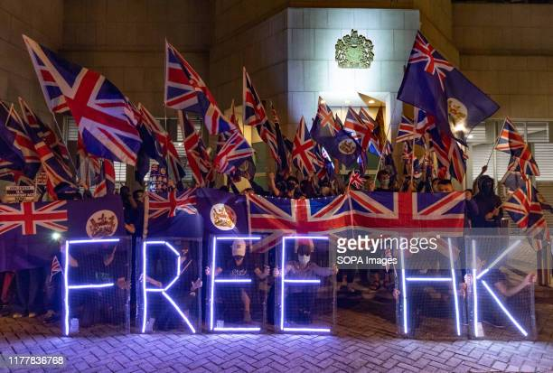 Masked protesters hold a 'free HK' sign outside the British Consulate Urging the British government to support the motion debate in House of Lords of...
