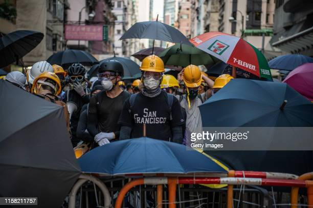 Masked protesters stand behind a makeshift barricade during a demonstration in the area of Sai Wan on July 28 2019 in Hong Kong China Prodemocracy...
