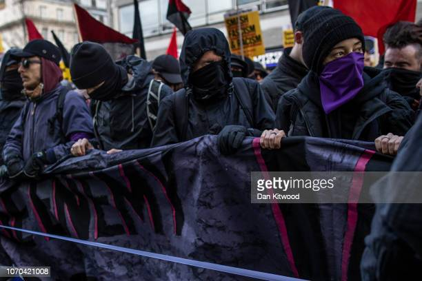 Masked protesters take part in a separate antifascism protest ahead of a UKIPbacked Brexit betrayal rally on December 9 2018 in London England The...